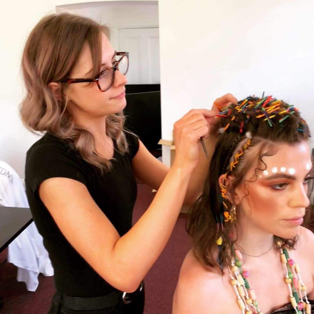 A hairdresser, Abbie Jackson works on a client's hairstyle.